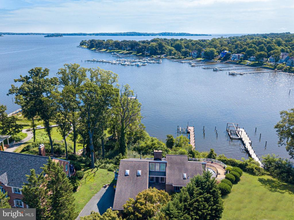 Savor the sensational panoramic Magothy River views from this contemporary home with 4 bedrooms, WATERSIDE POOL, expansive deck with unobstructed views plus a multi-slip deep water pier (6ft MLW) with boat lift just off the Magothy River on Cool Spring Cove.  Your fellow mariners will be envious of the close proximity from your pier to some of the best boating/fishing/entertaining the Chesapeake Bay and its waterways have to offer.  Inside, the sun drenched Living Room with skylights, soaring wood ceiling and 2-sided stone stacked fireplace are as awe-inspiring as the sweeping water views and the open floor plan, well-equipped Kitchen and adjacent Dining Room makes entertaining a breeze.  Choose one level living with the conveniently located main level Owner's bedroom suite or take advantage of the additional 2nd floor bedroom suite and spacious lower level Family Room with wood stove and sliding glass doors to the pool and waterside deck.  This property even offers the hard to find trifecta of public water, sewer & natural gas!  The pool and waterside deck area are not currently operational.  Located in the Blue-Ribbon Broadneck School district and just 5 miles to downtown Annapolis and Severna Park.  Convenient to Baltimore, BWI, Ft. Meade/NSA and Washington, DC.  You literally have the best this region has to offer in a 30-mile radius.  Be sure to view the Video Tour.  Welcome Home!
