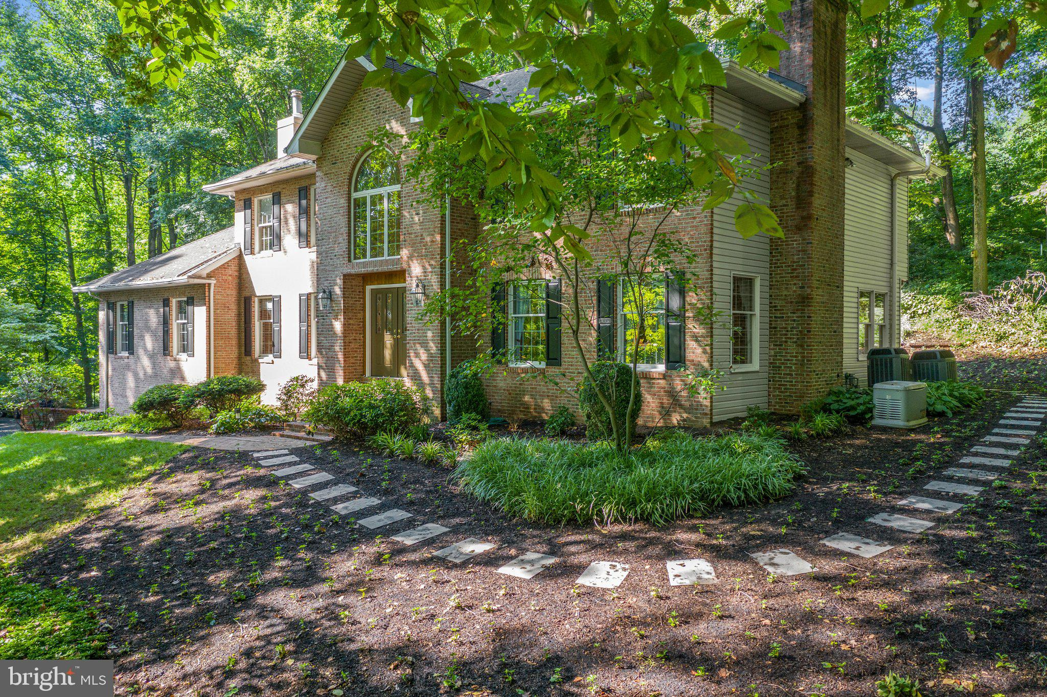 """The winding driveway will lead you to this gracious brick colonial, sitting on the most serene 2.8+ acres located in the heart of Pike Creek/Newark. You will be welcomed into this home through the double doors to the stunning two-story foyer. Flanking the foyer is the formal dining room to the left and a sunk-in living room to the right, which features a lovely raised hearth brick fireplace. Continue walking and enter the fully renovated gourmet kitchen, complete with an ample sized island, lots of granite counters, upgraded appliances and a wet bar featuring an under counter refrigerator. Around the corner from the kitchen is the well sized family room and it includes a stone raised hearth gas fireplace, recessed lighting and lots of natural light entering through the abundance of windows. Don't miss the flexible office area area off of the kitchen, showcases built-in bookcases and recessed lighting. The bright sunroom, first floor laundry room and half bath complete the first floor.  Ascend to the second level and enter the large master bedroom, which includes a third fireplace, walk-in closet and bathroom featuring a free standing soaking tub, two vanities, spacious shower and don't miss the  tray ceiling with up-lights featuring a hand painted """"starry-night"""" mural. There are three additional bedrooms and a renovated full bathroom, completing the second level. The lower level allows for a great theatre area, guest suite and full kitchen! The three-car bay garage allows for ample parking and there is an oversized parking area at the top of the driveway! The back deck is accessible from both the kitchen and sunroom making it perfect for entertaining friends and family while enjoying the gorgeous backyard.  This lovingly maintained and upgraded home is calling for you to call it yours!"""