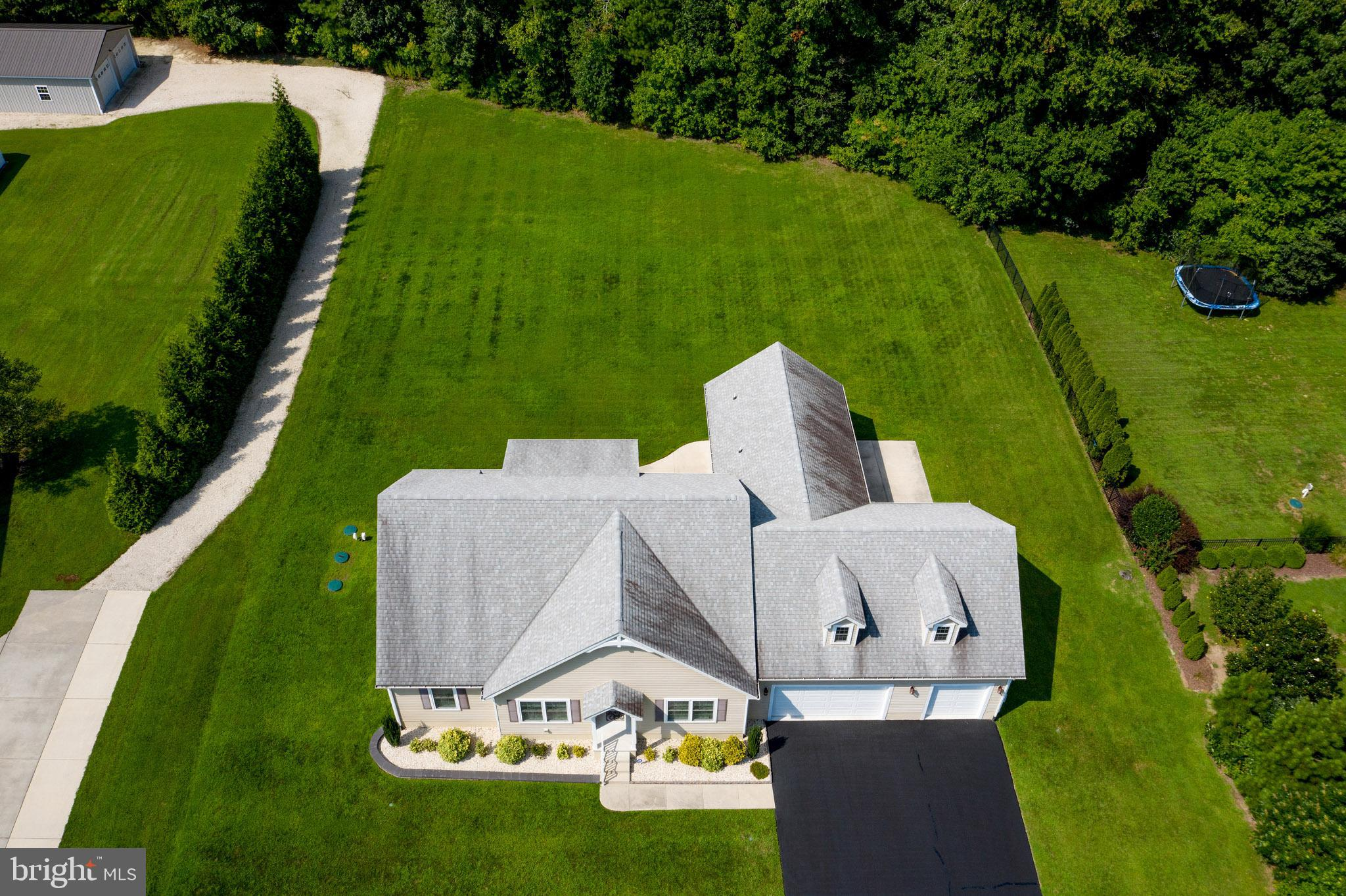 This delightful one owner home  is 8 years young, almost  1 acre of land, in a private cul-de-sac community AND  just 7 miles from Route 1 / Lewes area!  This 2300 sq ft. home with  3 beds, 2 full baths & an over sized  3 car garage has so much to offer -  9 ft ceilings, hardwood floors throughout  (except the bedrooms), Custom 3 inch Plantation Shutters on all windows, ceiling fans in every room,  lighted closets,  granite counters, extensive molding - including crown molding in the primary bedroom and formal dining room! As you enter the home, Main Entry way features a sizable room (with closet),  currently used as an office and a formal dining room to the right.  Both rooms feature double doors to open or close.  Continue into the living room where you will find a dramatic 16 ft ceiling.  Gather here or open the  French doors to enjoy the 18 x 12 tiled screen porch, including ceiling fan and a pull down shade.  This room offers a lovely view of your backyard. If you prefer the sun, step down to grill and sit on the patio! The modern kitchen offers expansive granite counters & cabinet space. Ideal for families who love to cook.  Center island, lighted pantry, and breakfast area completes this dream kitchen! Home has a split bedroom floor plan. To the left of the LR are two generously sized bedrooms and a full bath including granite vanity, sleek fixtures and a transom window adding even more natural light.  The Primary Suite is generous in size with almost 400 sq ft. Plenty of room to add a sitting area.  The primary bathroom continues with space and 9 ft ceilings & features granite vanity, double sinks, His & Her closets, 2 person shower, including rain shower head.  The laundry room is roomy enough to add a folding table. From this area,  step down into the over sized three car garage (36 ' x 27 foot), with plenty of storage, including stairs to a Bonus Room.  Appreciate this upstairs unfinished canvas to create a space special to you and your family!  More stor