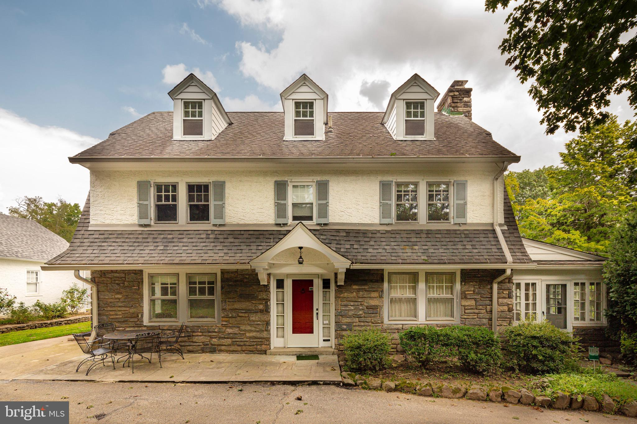 Beautifully situated stone residence on a mature planted lot with beds of roses.  5BR-3Full Bath- 2 1/2Bath Family home for 56 years- well maintained. Enter the house from the side portico door at terrace level to a center hall.  To the right of the center hall is the living room with hardwood floors, build-in book shelves and a wood burning fire place with a stone mantel.   Flanking the fireplace are sets of soundproof double doors.  Doors open to a beautiful bright 3 sided windowed sunroom  or a Private Office with Separate Entrance from the lower terrace.(was used for many years as a psychiatrist office) The center hall leads to an elegant dining room on the left with built-in corner cabinets of glass with wood detailing.  Enter the fully equipped kitchen from the dining room or hall.  The  breakfast area is sunlit. The rear door leads to mud room and pantry then to the outside terrace.   Second floor primary suite with hardwood floors, full wall of floor to ceiling closets and separate closets on either side of the tiled bathroom.  Two additional bedrooms with hardwood floors, lots of light and shared hall bath.   Third floor with 2 bedrooms with dormers and demi-fan windows with a walk-in cedar closet plus hall shared bath.   Basement has fully finished entertainment space with  wood paneling and linoleum floor and stairs to outside.  Built in bar in the entertainment space with full laundry, 2nd refrigerator, utility sink and workshop area with an additional powder room and large storage closet.  BRAND NEW ELECTRICAL SYSTEM and electrical panel just installed with three pronged sockets throughout  Outside has terraced area and front lawn area with flower beds and a  rear flat lawn perfect for croquet plus a separate 2 car garage with drop-down stairs to attic storage space.   Workshop area has full electric. Originally built in 1936 with all of the solid bones  and detailing