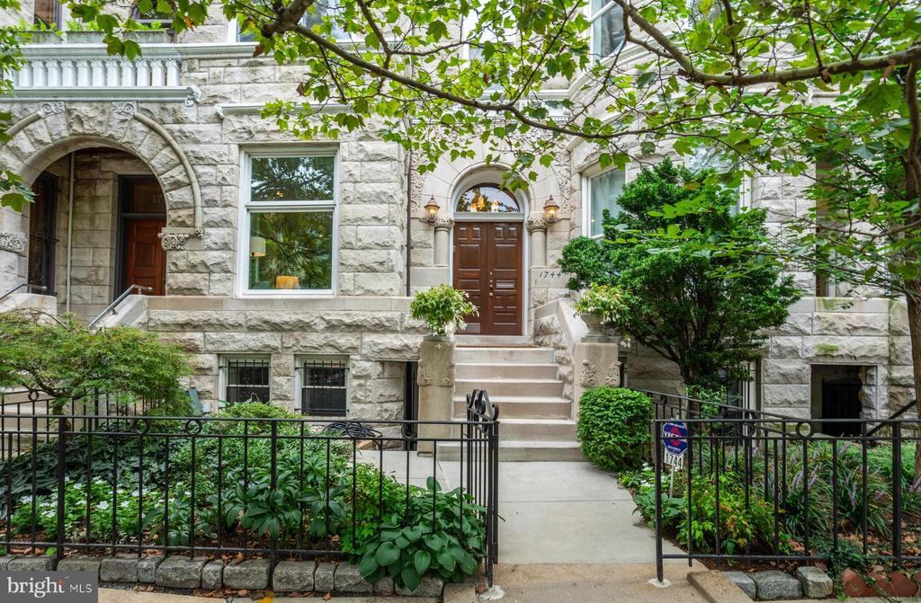 Welcome to this stately home with over 3,700 square feet of living space, two-car parking, a garage/carriage house, and a backyard oasis all perfectly situated on the leafy and desirable 1700 block of Q St., NW. In the heart of the historic Dupont Circle neighborhood, just steps to Metro, sidewalk dining, boutiques, cafes, shopping, art galleries, and much more.  This four-level brownstone, designed by the renowned D.C. architect Thomas Franklin Schneider, boasts bespoke detailing throughout and is rare and grand at 20' x 40' . Enter through the original solid ash door into the light-filled entry and the open-concept main level with soaring ceilings, detailed moldings, hardwood floors and the original fireplace -- one of seven in the home. The living room with 10+ foot ceilings and charming sunlit bay window is ideal for entertaining and flows into a chef's kitchen with dining area, oversized granite island, stainless steel appliances, custom built-ins and the show stopper -- a wall of floor-to-ceiling original exposed brick. Take a few steps from the kitchen onto the back patio to enjoy dining under the stars or walk down to the lower level stone patio. You'll feel like you've landed on your own private European terrace with a canopy of trees and plantings along with entertaining, dining and grilling spaces. A custom-made brass handrail leads to the upper floors, including a spacious owner's retreat with an en suite bathroom and two walk-in closets; two more large bedrooms one with a loft; a bedroom just right for an office, nursery or craft room; full hall bath; and a grand den  (or can be used as an additional bedroom) with custom built-ins and a delightful bay window seating area perfect for tea and a book. The lower level has pantry storage and a powder room for guests, as well as an apartment with private front and rear entrances and features a full kitchen with charming exposed brick, separate washer/dryer, bedroom, office/den, and a full bath -- well-appoint