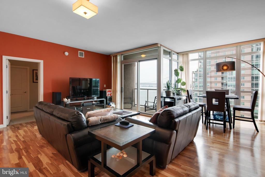 """Welcome home to Unit R1103 in the Regatta Building at Waterfront Square on the Philadelphia riverfront. Walking into this one bedroom plus den style unit, you are greeted by panoramic views of the Delaware River and Ben Franklin Bridge through the insulated floor to ceiling windows. During the day, the unit is brightly lit by the Southern exposure. At night, you are greeted by the beautifully lit spans of the Ben Franklin Bridge and shimmering water. This unit is set apart from others with 9' ceilings, extended 42"""" high cabinets, granite countertops, an undermount kitchen sink, and engineered hardwood throughout the open concept kitchen and living room area. A balcony with a sliding door overlooks the water and green space below. The bedroom features water views, a walk-in closet, and a spacious four-piece bathroom with marble floors and shower tile, granite top vanity, a large shower, and a Jacuzzi jetted tub. The open concept living area can be configured in multiple ways to meet your needs. A powder room near the entry contains a large closet with a brand new washer and dryer. This gated community includes numerous amenities including a deeded parking license, secured access system, 24/7 security, doorman, and a fitness center located on the river deck. The fitness center contains a 25 meter heated lap pool, hot tub, large gym, convenience store, and spa facility. The excellent location provides easy access to the area bridges, I-95, I-676, and the airport, yet provides a quiet and peaceful respite from the noise of the city. All utilities including heat and air conditioning and access to the fitness center are included in the low monthly fee. A community room off of the spacious lobby on the first floor, with views of the river, may be reserved for events and gatherings. Included in this fantastic price is a storage unit on the 2nd floor. If you're looking for luxurious, maintenance free living showcasing the best views in Philadelphia, then this is the place fo"""