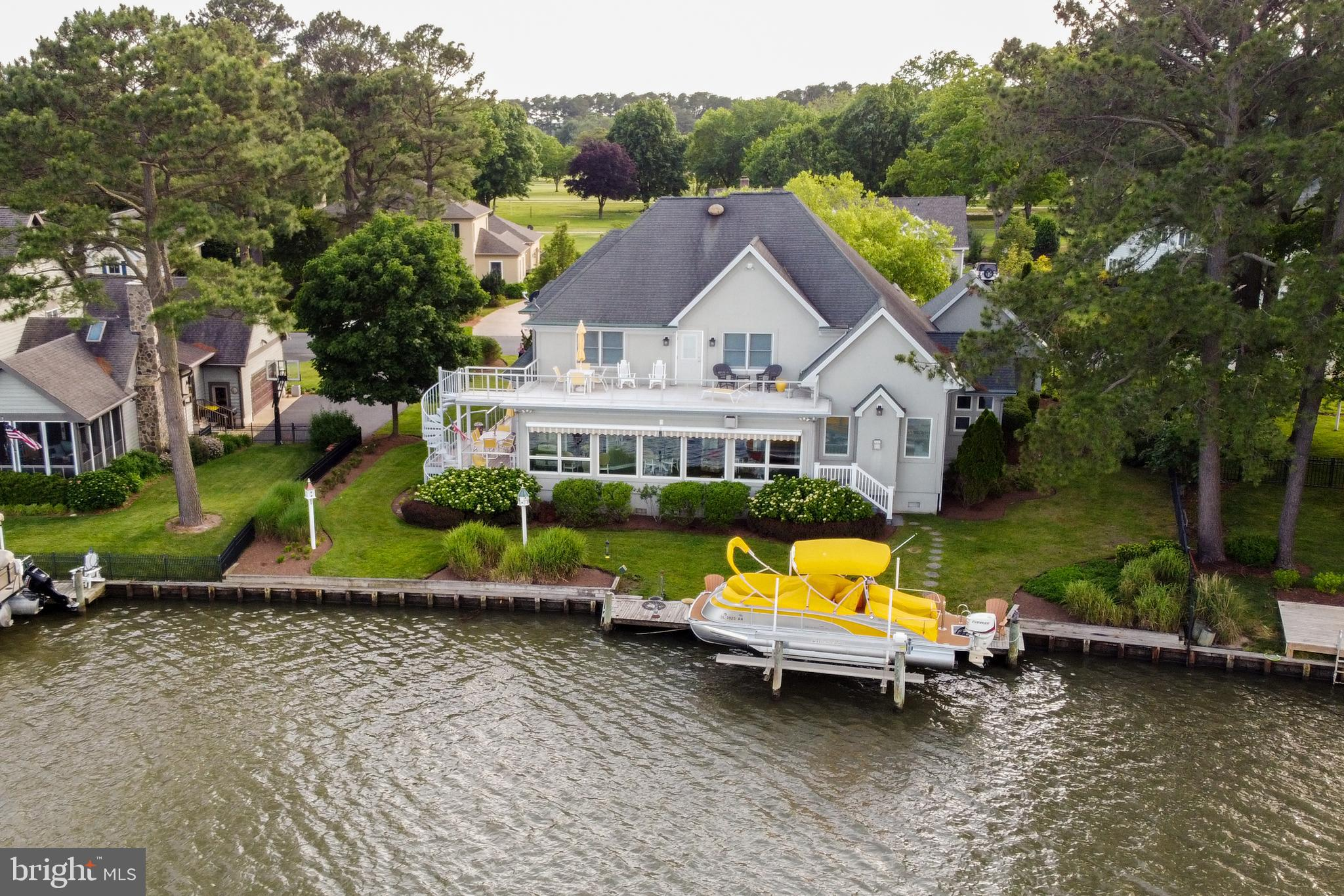 LUXE WATERFRONT LIVING! Life doesn't get any better than in this waterfront home in prestigious RBYCC. Hosting formal and informal get-togethers will be a dream with this contemporary, coastal home, from the grand foyer, to the beautiful living room, to the bright sunroom, to the chef's kitchen, to the cozy den, this home is exceptionally accommodating & showcases the property's scenic waterfront location! Warm-weather parties will flow effortlessly out onto the back decks, & private boat dock with the sparkling water & landscaped grounds providing a picture-perfect backdrop. Other highlights include five spacious bedrooms, including the first floor owner's suite with huge walk-in closet with marble flooring & luxe en-suite bath, hardwood & tile flooring throughout, Zodiaq countertops in the kitchen, three gas fireplaces in the den, owner's suite, & a double fireplace in the living and sunroom, and more (see attached features list)! Located in one of Rehoboth's finest communities, RBYCC offers many membership-optional amenities such as outdoor pool & tennis, golfing, and much more! Just a short drive to Rehoboth and Lewes Beach shops, attractions, and the beach! Call Today! Sellers can settle anytime , but do not want to move until the end of the  year.
