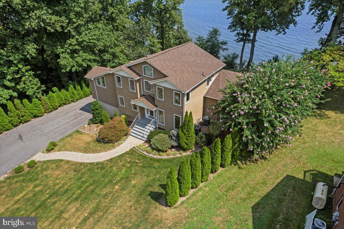 Are you looking for SPECTACULAR VIEWS OF THE CHESAPEAKE BAY? Price was just improved too!   Do you want a yard that affords lots of space for entertaining and no trees to block your view?  Do you want a huge deck off the back of the home to enjoy the panoramic scenes  year round?  The floor plan is open so the beautiful views are everywhere! The owners suite is on the main level as well as laundry facilities.  Look no further!!! But don't wait long! This home has been almost completely redone just for you!  Freshly painted, hardwoods redone, new carpeting, new roof, upgraded bath, upgraded kitchen and much more.  Walk up to the front door and  the first thing you will see is the  Chesapeake Bay right through  the glass door! This is the perfect first impression  for  a striking  waterfront home!  You will be amazed even before you open the front door! No flood insurance needed here as this home sits majestically  above the waters edge and you have a large grassed back yard leading to the water.  There is a small community beach for owners to use at the other end of the subdivision.  Contemporary architecture makes the best use of the space and the natural  views.  You will never want to leave home! A true TIMELESS COLLECTION HOME.