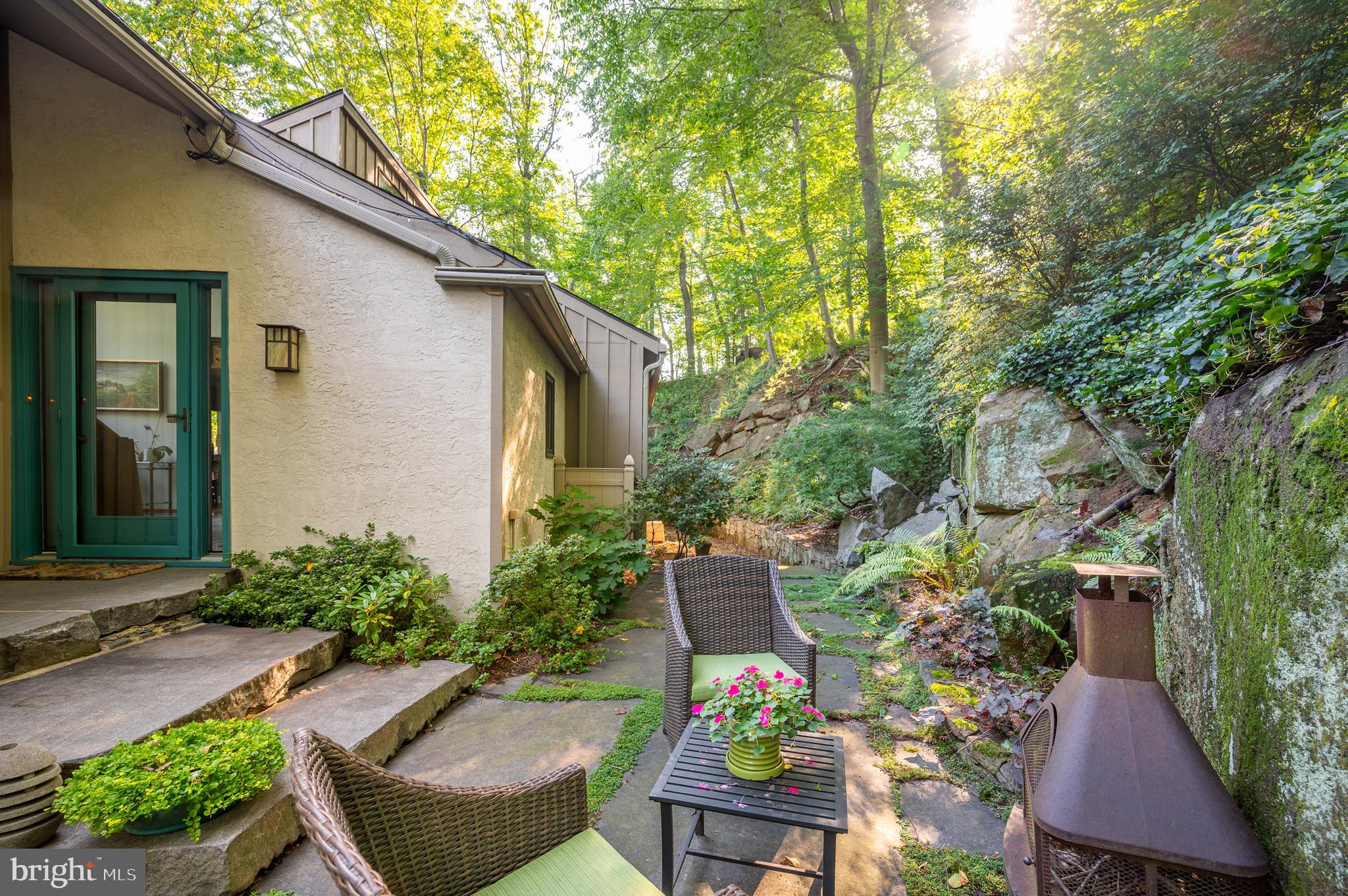 Nestled above the Brandywine River behind the Delaware Art Museum, this home is one of a kind. Set in the natural landscape of the area, this contemporary home is welcoming to all! After enjoying the water feature and sitting area at the entrance, step up onto the Brandywine blue rock stone steps to enter the spacious and bright foyer with a Vermont slate floor. With cathedral ceilings, the main floor features a living room with three sets of sliding glass doors, a fireplace with a slate surround, a dining area, a sitting area, a large powder room with a wall-to-wall marble countertop, and renovated kitchen. A large deck spans the back of the home and a lovely screened-in porch is located on the side of the home creating a relaxing, outdoor experience.  In the kitchen, enjoy the natural custom cherry cabinets crafted locally in N Wilmington,  Costa Esmeralda granite countertops, a tiger maple island top, heart pine floors, bookshelves, and banquette making it an eat-in kitchen. Preparing food in this kitchen is a pleasure with Wolf cooktop, Bosch dishwasher,  Wolf wall oven, Sharp microwave, Grohe faucet, Franke sink, and a Brisos stove vent. Step up a half flight into the expansive primary bedroom with three walk-in closets, natural views of the outside, and a renovated bathroom with granite countertops, dual vanity, walk-in shower with oversize tiles and two showerheads, and custom window plantation shutters.  Move to the lower level to find two bedrooms, one with a walk-in cedar closet, a renovated full bath with a walk-in shower, and a foyer with a laundry closet with a utility sink. A truly unique feature of this property is the Yurt! Walk up the stone steps using the hand-forged railing to a Yurt that has a skylight, HVAC, a deck, and a view of Alapocas Run State Park.  What a great space for an office, yoga studio, game room, music studio, or teen hangout! This home has amazing storage with a walk-in closet on the main floor, a partial unfinished area on the 