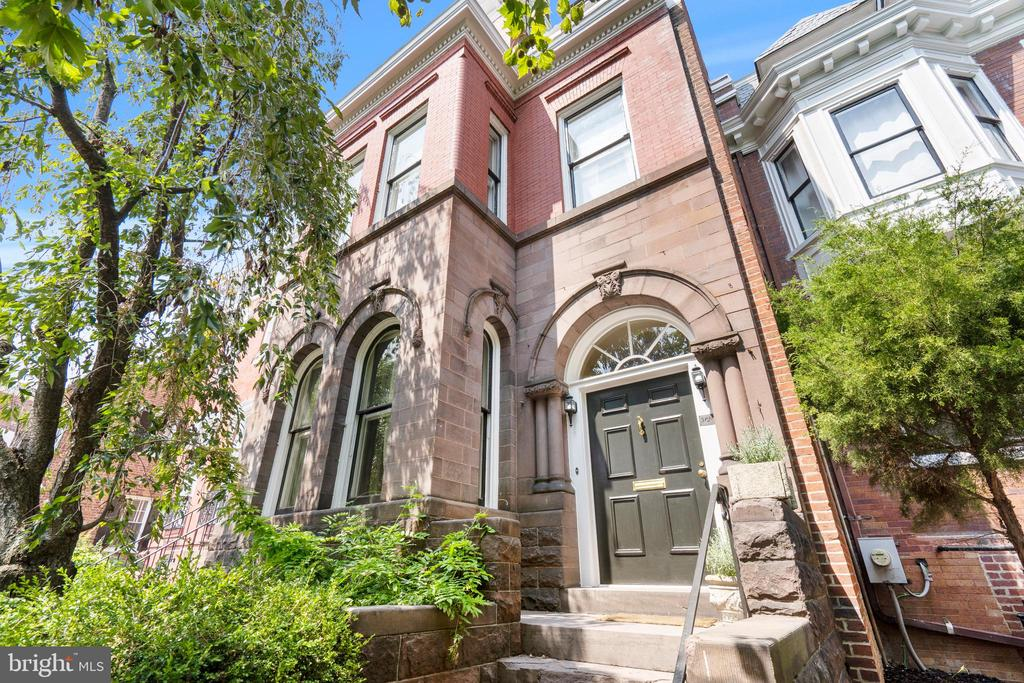 This historic brick and brownstone rowhouse is ideally located on a prominent block in Georgetown's East Village. The residence is set off the street and has a commanding south-facing façade. The house was originally built circa 1890 and features impressively high ceilings and exquisite original architectural details throughout including stain glass, transom windows, and elegant moldings. The formal rooms are of remarkable scale and offer spectacular opportunity for grand entertaining. The dramatic entry foyer has 11' ceilings and seamlessly transitions to the double parlor/living room. The room is graced with abundant natural sunlight and features a beautiful bay window and two fireplaces with attractive wooden mantles. The room can be completely closed off via two sets of pocket doors, both of substantial scale. Neighboring the living room is the sophisticated formal dining room. The eat-in kitchen, which is located towards the back of the house, has a paneled ceiling, Viking range, abundant cabinetry storage, and direct exterior access to the rear terrace and garden. There is also a full bathroom on this level. The second level features soaring 10' ceilings and includes three bedrooms, a full bathroom, library, and office. The remarkable primary bedroom is spacious and has a lovely bay window, walk-in closet, exquisite dentil molding, and a fireplace. It adjoins the attractive library, which features abundant built-in bookshelves and storage space. Both additional bedrooms on this floor have large closets. The third floor has two more bedrooms, another full bathroom, a study, and a large walk-in hall closet. The fully finished lower level is expansive and offers a large family room or generously sized office with a fireplace, a secondary kitchenette, full bathroom, laundry room, and additional storage space. The lower level also provides access to the rear terrace and garden. The garden is fully fenced and extraordinarily private, making it the perfect place for 