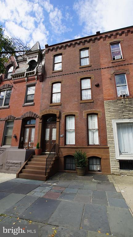 GRAND HISTORIC BROWNSTONE WITH DEEP YARD ON SOUTH BROAD. Space, location, possibilities are what this captivating 18-foot-wide, three-story home has to offer. Wide steps and ornate brownstone frame the double doors that welcome you into a foyer with beautiful historic tiles. The entry hall has a magnificent floor-to-ceiling mirror framed with gilded carved wood. A long parlor/living room is to your right with a red marble mantel, oak floors, large double-hung windows that retain the foldable split shutters designed to tuck into the window frame when open. Down the hall on the first floor are three rooms in a row. Currently, used as a family room (with a 1st fl powder room), then formal dining room, then spacious kitchen. The kitchen was updated five years ago with stainless refrigerator and stove. A window over the sink looks out into a deep yard. In this home, you could grow a green oasis steps away from the bustle of the city. The two upper floors have eight rooms and two bathrooms combined, with more wood floors and original details. If you want space, this is the house for you. The basement is full and deep with a washer, dryer, and several options for storage. The location is central. Making the ease of city life part of your lifestyle. If you take the 20-minute walk to City Hall, you will pass Target, Sprouts, numerous restaurants, and theaters, including the Kimmel Center and Academy of Music. Or you could jump on the Broad Street subway, 7 min to City Hall, or 20 min to Citizens Bank Park and a Phillies game. Walk to Passyunk Square for a James Beard awarded restaurant or a few blocks up Wharton Street to your choice of cheesesteak shops and the Italian Market.