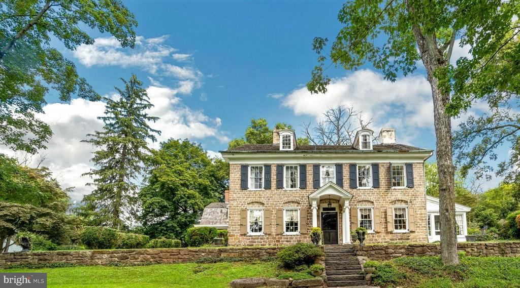 A Georgian Manor House – Circa 1740's located near Valley Forge and recognized as one of the oldest Georgian style homes in Chester County.  Rich in Revolutionary War history, Moore Hall is a stately stone mansion on 13 plus acres near Valley Forge Park.  This National Historic Register property served as officer's quarters during the Revolution and in the 1800's, a stop on the Underground Railroad.  Because five miles separated this historic site from the Encampment of the soldiers, it was it not included in the 1430 acres set apart in 1893 as Valley Forge Park. George Washington was here! In 1778, Moore Hall was the meeting place of a joint sub-committee of Congress. It was here that George Washington stood to defend himself against allegations that he was not competent to lead the American forces. The house demonstrates the typical five bay center-hall, two-floor plan of Georgian architecture.  The center hall is divided into a front hall and a stair hall by two fluted Doric pilasters.  Most of the interior detailing is original with high ceilings, deep crown moldings, chair rail, paneled window, deep windowsills, random width floors and doorways with eared architraves.  Off the center hall is the formal dining room featuring a carved marble fireplace centered in a paneled wall a unique cabinet with arched heads and keystones above both the cabinet and symmetrical door on the other side of the fireplace.  On the opposite side of the center hall is a large living room with a marble fireplace, built-in cabinets, and shelves, four large windows, chair rail and magnificent crown moldings.  From the formal living space, two French doors lead to the relaxing sunroom with a ceiling made from original barn beams.  It is a perfect place to relax and enjoy this peaceful country setting!  Just across the hall is a comfortable den with a fireplace housing a Vermont Stove, perfect for those cold winter nights.  The breakfast area, kitchen with stainless refrigerator, range an