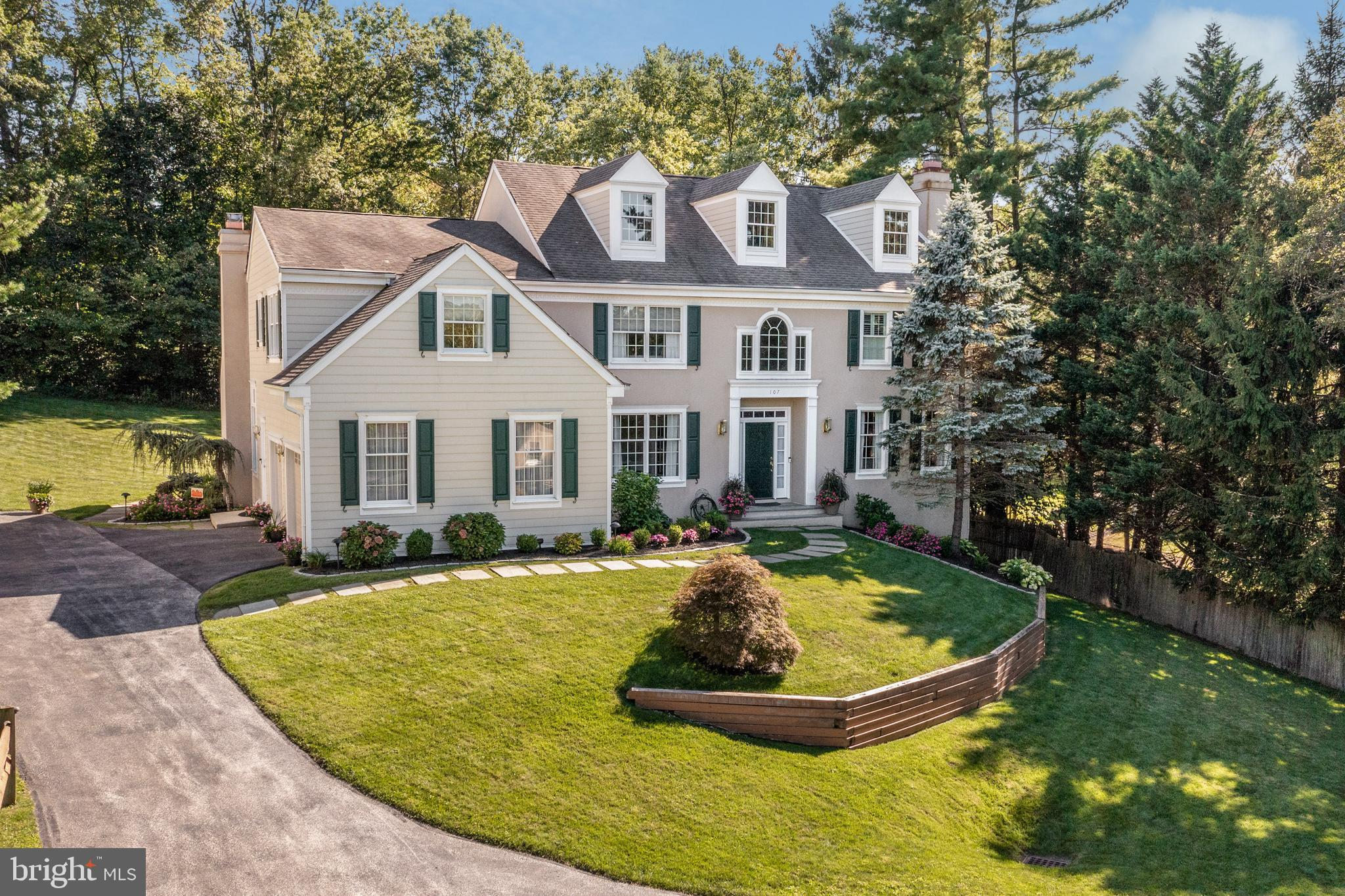 This classic, walk-to-Wayne colonial marries an elegant and spacious interior with a beautiful, calming exterior. With four bedrooms and three full bathrooms, as well as a finished lower level and attached two-car garage, you have the room you need in a location that is also ideal: within the sought-after Tredyffrin-Easttown School District and proximity to Main Line towns and all they offer, along Route 30. The attractiveness of the home begins with a pretty walkway, flanked by mature plantings and leading to a gracious front door and entryway. The elegant foyer, topped with distinctive windows and with two closets, leads to the living and dining rooms on the right. The living room, with a white-mantel fireplace, has generous windows, high ceilings, and distinctive crown molding. The dining room features hardwood floors and wainscoting. To the left of the foyer is a home office next to a full bath with stall shower - convertible to a first-floor bedroom with bath if desired. The kitchen is an ideal destination for both preparing everyday meals and hosting. It brims with attractive features, including granite countertops, a center island with bar seating, lovely white cabinets, some with glass doors, and tumbled marble backsplash. An elegant bar area with separate sink adds to the prettiness of the room, while professional, stainless steel appliances, including a gas Wolf oven range, make cooking easy. The adjacent breakfast/morning room is sunny and bright, with sliders that open to the spacious deck and backyard. The ongoing spaciousness flows from the kitchen, leading to a carpeted family room that has a white-mantel fireplace and two-story, vaulted ceiling with fan and two skylights. Both the pantry and laundry area are next to the kitchen, with convenient garage access as well. Ascend to the second level - The main bedroom, carpeted and with two walk-in closets and a separate sitting area, features an updated bathroom with double vanity, a soaking tub, and walk