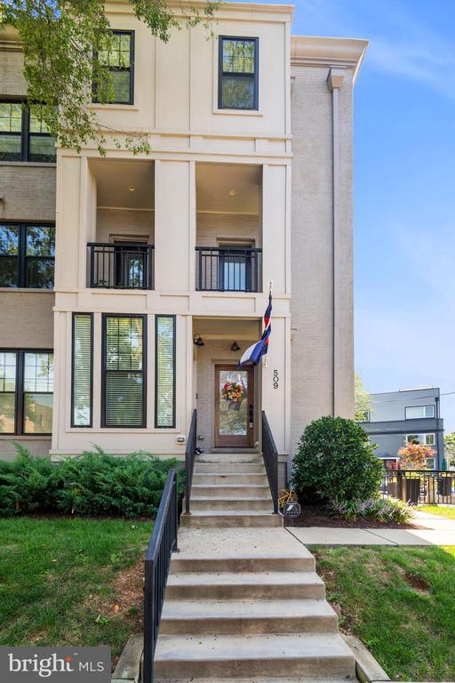Open Sunday Sept 19 1-3pm. Check out the 3D Virtual Tour! This spacious, contemporary end-unit townhouse in Brookland, built in 2017, features 1,600 SF across 3 living levels and includes 4 bedrooms, 3.5 baths, 3 balconies plus a private side patio, and a covered carport for 1 vehicle.  With 3 exposures, a sun-drenched floorplan boasts wide plank hardwood floors, high ceilings, and luxury finishes throughout. The main level includes 1 bedroom, a wet bar with a beverage fridge, full bath, and direct access to the private, covered parking space in the rear. The second level is highlighted by a gracious living room with French doors to a rear terrace, a gourmet kitchen with gas, stainless steel Kitchen-Aid appliances and marble island, high ceilings, quaint front balcony plus a separate side Juliet balcony, and a powder room. The top level features 3 bedrooms and 2 full-baths, including the master suite showcasing an en-suite bath with dual sinks, marble flooring, and rain showerheads. The top floor is complete with front-load washer and dryer in the laundry closet. Outside, the side yard has been upgraded to include a private, fenced patio, perfect for outdoor entertaining. With a low condo fee and located just 0.7 mile from the Rhode Island Ave-Brentwood Metro and 0.8 mile from the Brookland-CUA Metro (both Red Line), this home is just moments from endless retail, restaurants, nightlife, breweries, and the Edgewood Recreation Center.