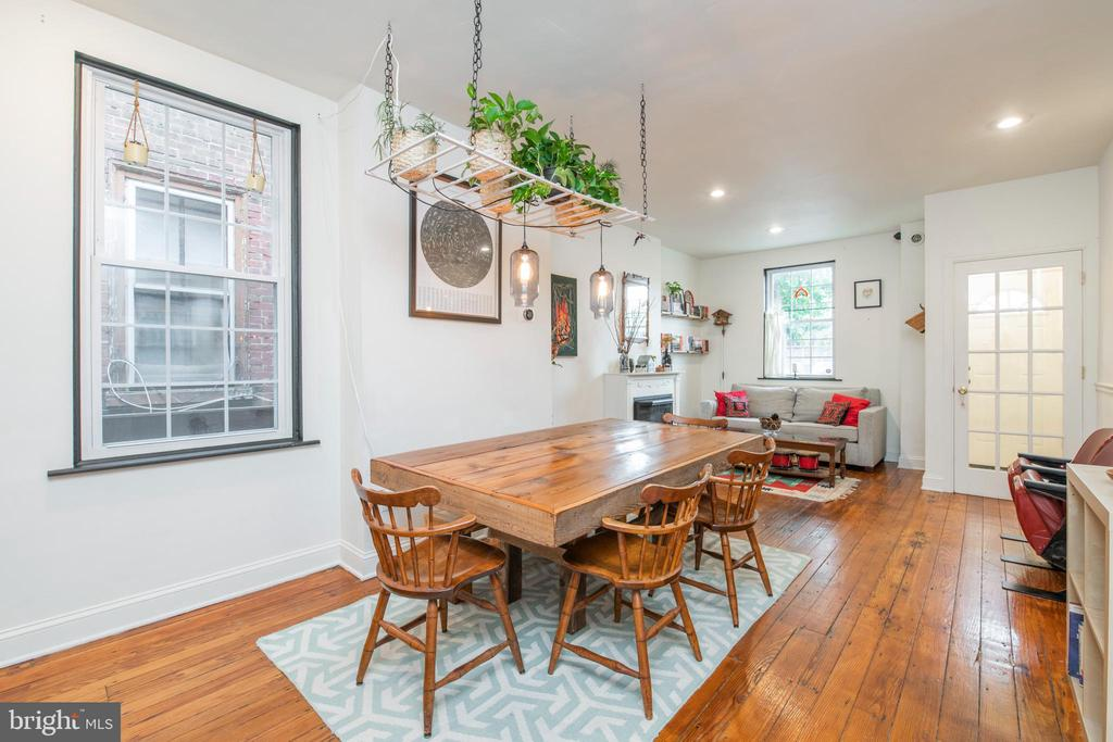 This light and airy Fishtown home is loaded with extras not typically found in a city rowhome: roomy bedrooms, tons of windows and an enormous backyard space. The first floor features refinished wide-plank pine flooring, a sweet gas fireplace set into the original mantel anchoring the living room, an industrial-cool light fixture/plant shelf above the dining area and the often-elusive coat closet. There's a spacious ceramic tiled kitchen with plenty of storage in the solid wood cabinets, granite countertops for prep, room for an island (or dining table to make it an eat-in) and extra tall windows perfect for container herbs. Keep the rest of the garden outside in the awesome backyard, where there's more than enough room for dining for six and a firepit with seating. Low-maintenance hardscaping meets a perimeter garden with retaining walls that offer more seating, and there are already blackberry and raspberry bushes alongside a mature shade tree. Both bedrooms upstairs are bright and sunny, benefiting from two exposures, and feature ample closet space. In between is an exceptionally large ceramic tiled bath with soaking tub and rain showerhead, wood vanity with vessel sink, built-in shelving for linen storage and an oversized window. The basement offers plenty of room for storage and houses the full-size washer and dryer. Tucked away on a cute little side street, this sweet home is across the street from bonus off-street parking, a rarity in this neighborhood, and there's a locked gate to the breezeway, great for bike storage or directing guests to backyard hangs. Located close, but not too close, to Frankford Ave, this home puts the best of Fishtown at your fingertips.