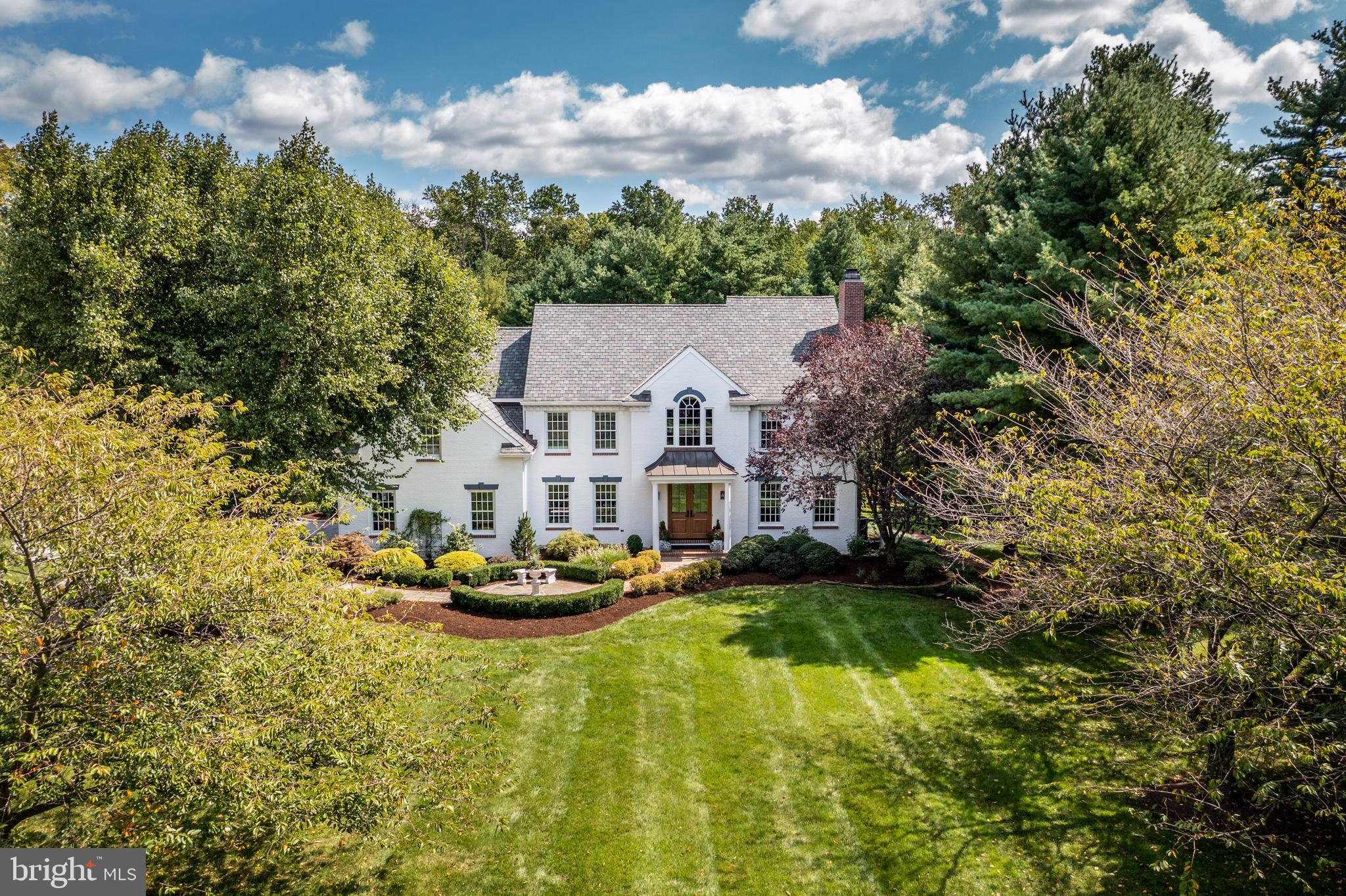 The beauty and elegance of this home in Malvern, located in the community of Fox Ridge, is hard to overstate. Situated in a lush, private setting with mature landscaping, this private oasis has a gorgeous, inground pool. The interior of the renovated, meticulously cared-for home, with its gracious touches including a Palladian window, hardwood flooring, and two fireplaces, is welcoming and lovely. And, with a newly renovated exterior, including roof and Hardie plank siding, it is built to last. The home's location, within the excellent Great Valley School District and close to all major thoroughfares and the town of Malvern, couples warmth and beauty with an ideal setting.  A beautiful and expansive lawn leads to the front entrance and its two-story, dramatic foyer, with marble floor. The formal living room, with its custom millwork, white-mantel fireplace, and oak flooring, flows into the dining room via French doors. Also a lovely space, the elegant dining room has oak flooring, large windows, and a stunning, coffered ceiling. The home's kitchen overflows with numerous upgrades, perfect for beginner cooks and experienced chefs alike. Special amenities include a six-burner Wolf stove and quartzite countertops. It is a gorgeous room to behold, with its black walnut center island with bar seating and complementary dining nook. Special cabinets with unique hardware, as well as distinctive backsplash and lighting, are wonderful touches. The open kitchen flows seamlessly into the family room, with its cathedral ceiling, white brick fireplace, pretty floors, and large windows. The first level has a powder room as well as an office, with large windows and hardwood floors. The laundry/mudroom has access to the three-car garage. From the center hall, a gracious staircase leads to the second level: a well-planned space with a main bedroom and bath, three additional bedrooms, and two renovated, beautiful hall baths. The main suite is a luxurious retreat, with its sumptuous, e
