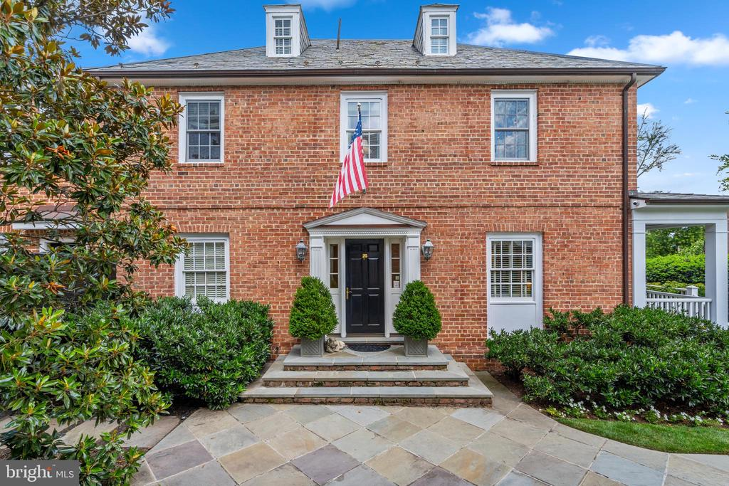 This spectacular fully detached brick residence is on an impressive .362 acre lot, ideally located on one of the quietest blocks in Georgetown's desirable East Village. The house is a rarity among Georgetown's primarily rowhouse-lined streets, perfectly situated on a prominent corner lot consisting of three separate parcels. The expansive flat lots are extremely private, concealed behind mature shrubbery and fencing. The house lives horizontally, providing generously-proportioned formal entertaining rooms, while suitably maintaining comfortable family living spaces. An abundance of natural sunlight illuminates the entire residence from large windows on four sides throughout. The gracious entry foyer provides seamless transition to numerous rooms on the main level. An elegant living room with a wood-burning fireplace opens to the lovely formal dining room. The well-appointed gourmet kitchen has high-end appliances, a built-in desk, and a large center island with breakfast bar seating. It opens to both the windowed breakfast room and the exceptional family room, which has a built-in media cabinet and four separate windowed French doors to the rear terrace and yard. There is also a light-filled den and the added convenience of a mudroom with a powder room with two separate pantry closets. The second level is expansive and offers four bedrooms, each with their own private en-suite bathrooms. The remarkable primary suite has a walk-in dressing room and a marble bathroom with dual vanities and a frameless glass shower. All other bedrooms on this floor are spacious and provide wonderful closet space. The third level loft/bedroom is generous and has a full bathroom and abundant storage. On the lower level of the house, there is a notable media/recreation room with a projector and built-ins. There is also a sixth bedroom, sixth full bathroom, laundry room, service bathroom, and excellent storage space, including a concrete enclosed vault storage room and an oversized walk-in