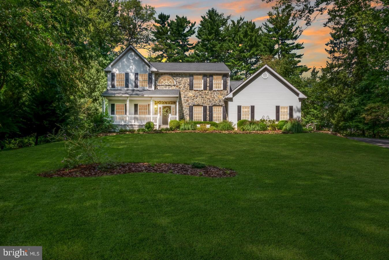 A stunner on Spring Lake Ave.! Nestled on 1-acre enclave in N. Wilm. and enveloped in aura of tree-lined privacy, this 4BRs/2 ½ bath stately stone/gray siding home with outdoor oasis is magnificently perched on gently sloping, landscaped lawn with winding driveway, and touts all-around appeal. Stone-stacked beds of shrubs line stone sidewalk which leads to white railed, elevated front porch that is roomy enough for pair of chairs and exudes welcoming ambiance. Home's upgrades include new BRs carpet (2021), recently renovated kitchen, new roof (2018), new HVAC (2016) and more! Front door opens to floorplan of dramatic angles, volume ceilings, oversized entrances and open spaces, while golden polished hardwood floors ground this dramatically designed home. Foyer features striking dual turned staircase, textured neutral-colored walls and crown molding. Beyond foyer is hall to kitchen with PR of distressed vanity with vessel sink, brushed gold hardware, new designer ceramic tile floor. 2 windows on front wall and stylish barely-there 2-tone custom painted walls of cappuccino/café au lait colors graces walls of formal LR to left of foyer, while opposite is equally impressive DR that boasts bronze wrought iron chandelier and matching windows and same custom painted walls, creating balance across front of home. Short hall off DR has closets on both sides and leads back to hub-of-home and heart-of-every gathering! Expansive and elegant hardwood floored kitchen is seamlessly linked to FR and stretches across back of home and together rooms echo openness and brightness of front of home. Gorgeous quartz countertops and farmhouse sink are favorably fused with creamy linen-colored cabinets with glass hardware/glass front upper cabinets with under cabinet lights. Subway tile backsplash with diamond accents is paired with sleek SS appliances. Center island with bar stools is highlighted by trio of pendant lights and offers comfortable and casual perch for dining around-the-clock. 