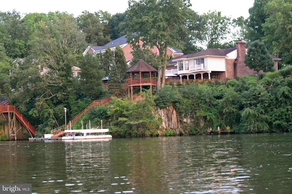"""Breathtaking  Occoquan River Waterfront Property with  Backyard Oasis & Scenic Views!  Property is not located in Flood Zone.  Private floating boat dock, 13,000 pound boat lift with 23ft water mean depth. Custom IPE exotic wood has exceptional density and natural oils last up to 50 years. Beautifully designed gazebo surrounded by professional landscape and expansive partially covered/ uncovered patio are the perfect setting to host weddings, special events, cookouts, boat rides, fish, swim, kayak or simply kick back and relax on the 12X32 dock. Completely renovated and custom inside and out that's felt from the moment you open the solid cherry wood French doors, custom kitchen cabinets and gleaming hardwood floors throughout. Panoramic views from the sunroom and primary bedroom addition complete the main level. Walkout lower level boast 7.5"""" wood plank floors throughout, includes spacious recreation living area, cozy gas/wood fireplace, wet bar, two bedrooms, office with built in maple desk and built in bookshelves plus additional storage area under staircase. Accommodating watercraft concrete driveway leads to oversized 900 sqft tandem garage, separate concrete lead walk to a backyard paradise. Rarely Available Premium Lot on Occoquan River last standard sale in 2007. Convenient location is a breeze to get to Historic Town of Occoquan where you can dine, shop, visit museums and art galleries or paddle over to the Occoquan Regional Park across the river where you'll find outdoor activities from bird watching, hiking trails, volleyball court, batting cages, picnic shelters, memorial sites and a quaint café. For avid boat lovers, this navigable waterway is only a short boat ride away to the Potomac River, National Harbor, MGM, DC, Georgetown and beyond! Easy access to 1-95, Prince William and Occoquan Harbour Marinas offer boat slips accommodations, indoor/outdoor dining/bars and live entertainment. 165'x20' Concrete driveway accommodates 80"""" boat.  No HOA &  Brand N"""