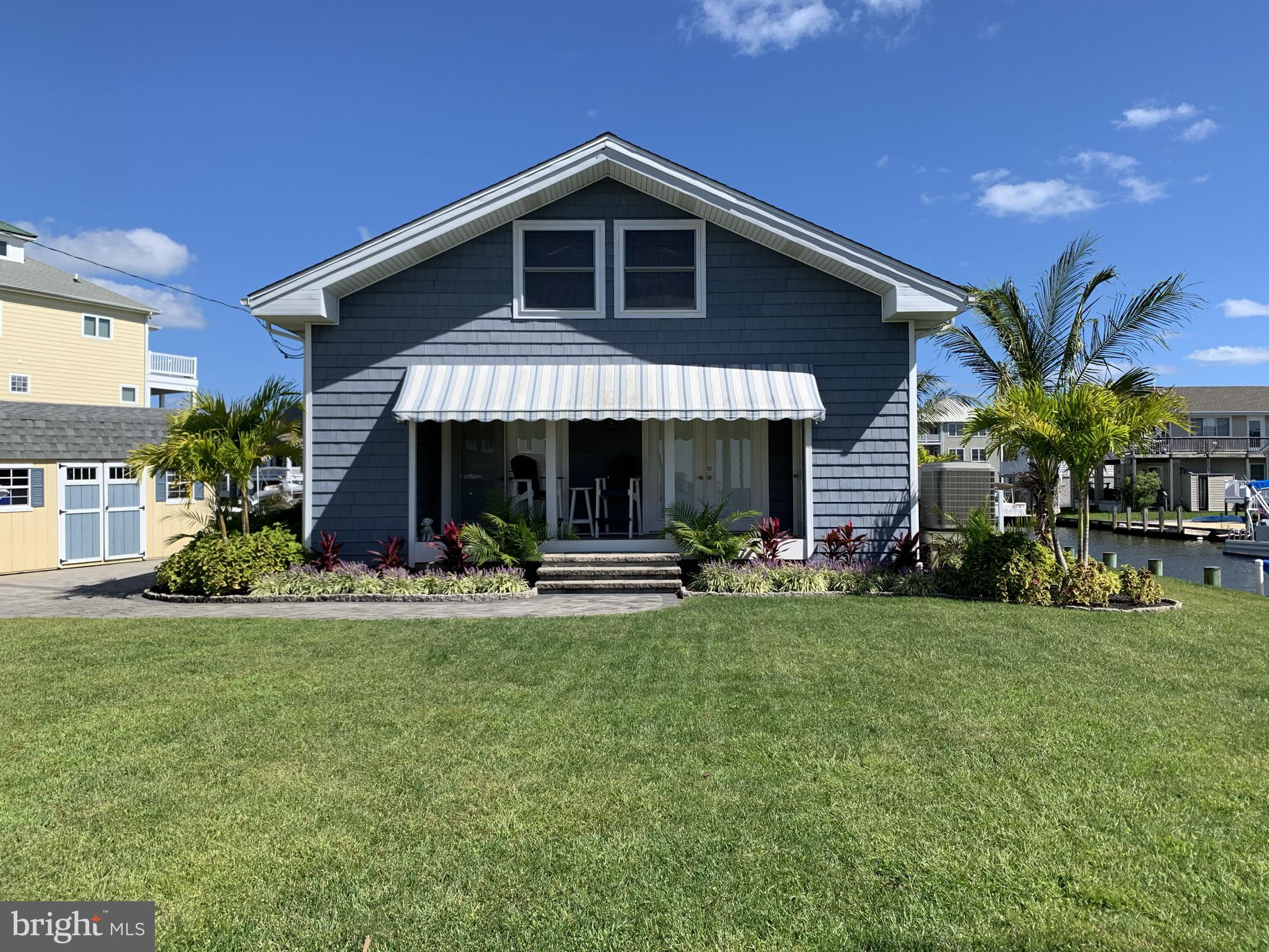 Beautiful, well maintained coastal cottage on unique two -sided waterfront lot boasting 150 ft +\- of bulkhead and water frontage, with canal and bay view less than one mile to the Atlantic Ocean and the Delaware beaches. Rich dark wood floors, open beam ceilings, and a comfortable, open Key West vibe interior completes this cottage. The outdoor impeccable hard-scape and tropical landscaping,  completes the home. The perfect location- close to the beach, abundant boat dockage and easy deep water access to the Big Assawoman Bay and the Ocean City back bays and inlet.