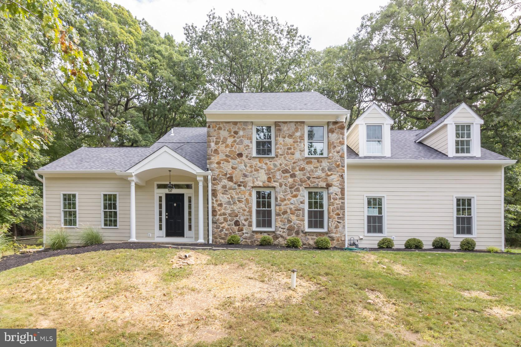Welcome to 432 Alderbrook Drive, a completely renovated 4 bedroom 2.5 bathroom colonial home with a contemporary flair on the Main Line in highly sought-after Wayne, PA.  This home sits high at the end of a cul-de-sac street on a large lot (over an acre), including a serene wooded area with several mature oak trees, and abuts the spectacular McKaig Nature Center, an 89 acre wooded preserve with 3 miles of hiking trails.  A two-story foyer entrance and beautiful hardwood floors that span throughout the home greet you as you enter this wonderful home. The theme of this home is natural light, pouring through the home's many skylights, sliders, and windows!  To the right is the formal dining room adjacent to the kitchen, perfect for holidays and family gatherings!  To the left is the family room with impressive vaulted ceilings.  Continuing on, the living room has sliders to the fenced in yard (great for four-legged family members!) and a gorgeous field stone fireplace surround with a wood beam mantle.  The living room is open to the gourmet kitchen, where you can enjoy stainless steel appliances (including a professional-style gas range), quartz countertops, island with bar-stool seating, and an abundance of soft-close cabinetry complemented by the sleek subway tile backsplash.  Off the kitchen is another set of sliders to the stone patio, where you can dine al-fresco and overlook the flat backyard and mature oak trees.  Back inside, an updated powder room with marble tiles and a mudroom/laundry room with utility sink and W/D hookup and access to the 2-car garage complete the main level.  Upstairs, find four spacious bedrooms and two full bathrooms. The luxurious master bedroom features a spectacular sky-lit en suite bathroom with a stall shower, large quartz countertop dual vanity, porcelain tile floors, and neutral finishes. The large walk-in closet offers a blank template to design to your liking with extra storage space for your winter clothes!  The other three gen