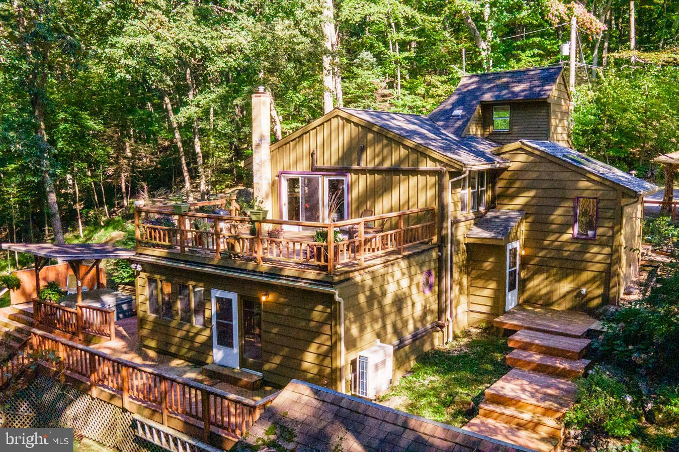 Are you looking for a non-traditional home that is far from ordinary? Do you desire a peaceful location amongst a natural landscape on 2+ acres where you can spend your time enjoying the little things that life has to offer? You now have a rare opportunity to be the new owner of this contemporary cabin that is situated in a natural setting amongst mature trees. It is located at the end of a private road in the Perkiomen School District. The wrap-around multi-level deck offers over 3,000 square feet of space to enjoy the wildlife and beauty of mother nature. Inside you will find quaint living spaces with vaulted ceilings and exposed beams that add authenticity and overall, a very regal feel to the home. An artist would love the amount of natural light through the abundance of windows and skylights to show off their art or simply to be enjoyed by anyone that loves a bright and airy home. The floor-to-ceiling brick fireplace with slate mantel is the focal point of the dining room making it a perfect place to admire a snow-covered view while enjoying a comforting meal. The natural knotty pine floors complete the feel and luckily, continue throughout most of the living spaces. The generously sized kitchen is open to the dining room and living area which is great for entertaining. If you are someone that believes a home cooked meal is better than anything else, you will love the abundant prep and storage space, along with the newer appliances. It offers slate counters, a double bowl sink, glass front cabinetry, a 5-burner gas stove, dishwasher, a side-by-side refrigerator/freezer and additional built-in storage shelves. There is also a separate morning room/office with skylights and sliding glass door to the deck. The cozy living room area could double as an artist studio as it creates a sense of ambiance with a built-in bookcase, cathedral ceiling, inspiring views, and a spiral staircase to the loft/office/studio. This main level also promotes a guest bedroom with pine f