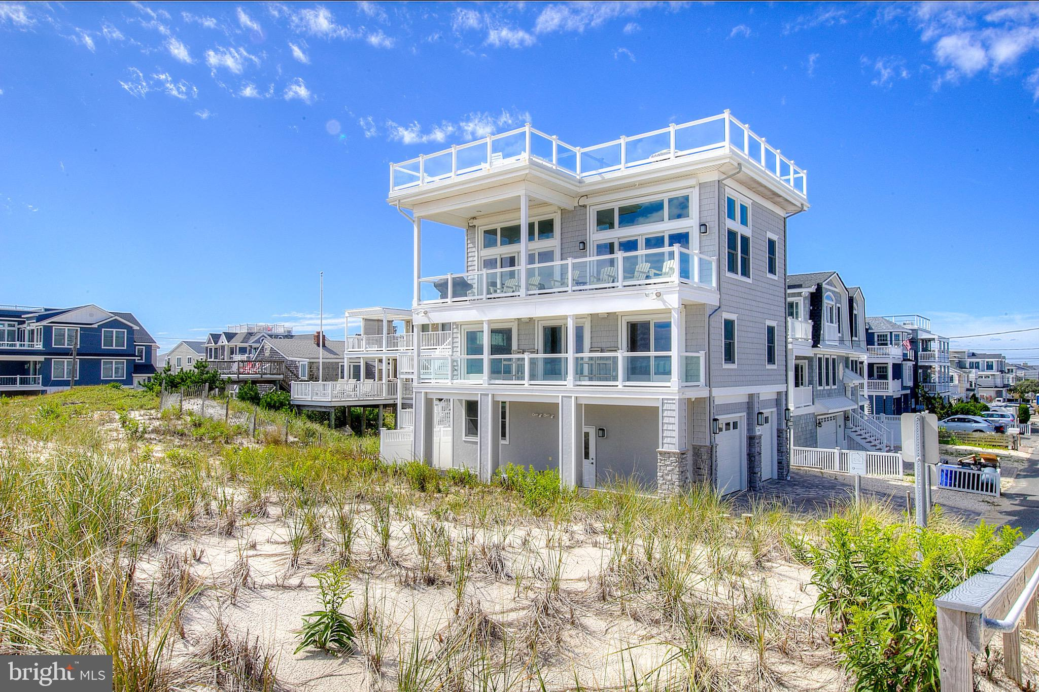 Steps from having your toes in the sand this OCEANFRONT single family home is located in The Peahala Park section of Long Beach Township. This reverse living home offers 3 floors of living space. The first floor is equipped with a sizable bedroom, full bathroom and laundry room. The 3 stop elevator makes reverse living an ocean breeze. The second floor features 4 bedrooms including an ensuite with deck access and ocean views. The open concept third floor offers a living room with a gas stone fireplace, a dining room and gourmet kitchen featuring stainless steel appliances, a tile backsplash and dazzling Quartz countertops. Enjoy panoramic ocean views and watch the sunrise from each of the 3 decks including a rooftop deck equipped with a 8 person hot tub. Some other home features include, engineered hardwood flooring throughout, an outdoor shower, 2 tankless water heaters for maximum efficiency, staircase riser lighting, remote control shades/storm shutters, a sonos speaker system throughout and a central vac system. This home is being sold turnkey furnished. Just pack your bags and start enjoying all Long Beach Island has to offer. Don't miss the opportunity to own your very own oasis in the sand at Sand Dune Lane.