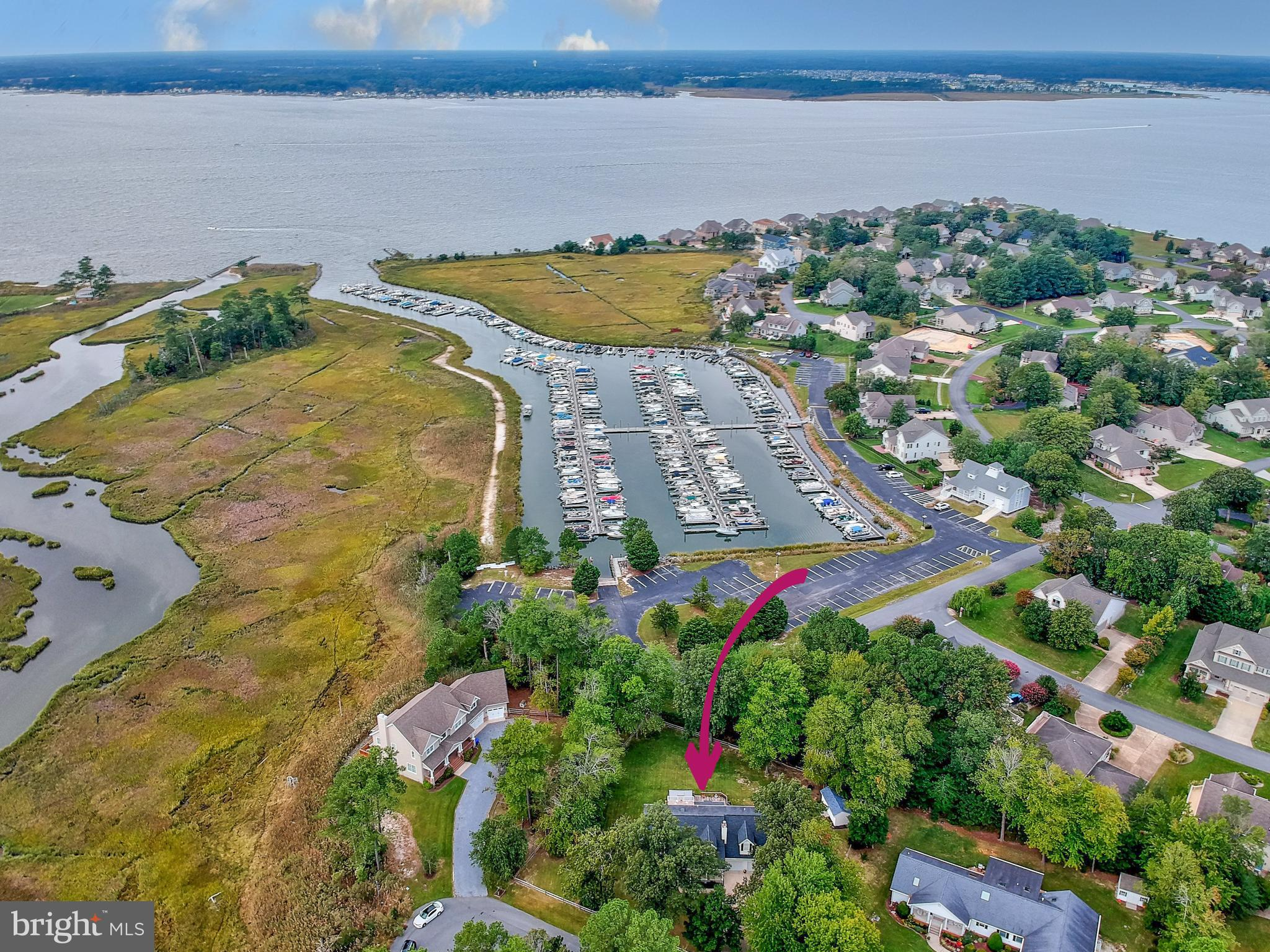 Surrounded by water, wetlands, and views of the marina and Indian River Bay all on 1/2 acre...Welcome to this spacious and attractive home offering 5 Bedrooms and 3.5 Baths, a 2-car garage plus large detached shed - in a small private community with easy access to Bethany Beach.  There is also a boat slip which may be purchased separately! You will love the peace and quiet that surround this location as you walk up to the large covered front porch.  Three large living spaces on the main level provide many options!  The front living area offers a wood burning fireplace and a view of the kitchen.  Ceramic tiled floors lead to the kitchen which  is perfectly located in the center of the home and has ample room for dining or lounging - either at the breakfast bar or the adjacent sitting area.  The kitchen offers a great work triangle with plenty of counter space, wood cabinets, and a view into the rear living space.  Tucked away off the kitchen is a mudroom with full size washer and dryer, cabinetry and powder room, as well as easy access to the oversized garage (23.5x24) with extra refrigerator and storage cabinets.  The rear great room is filled with natural light and features built-in shelving, wall-mounted TV and wired surround sound.  Access the large (14x33!) rear deck to fully enjoy the generous lot size and marina views.  A screened gazebo is the perfect retreat and the large backyard is ready for fun activities.  A first floor Master Bedroom with beautifully updated en suite bath is situated along the left side of the home.  Head upstairs to a central loft space that overlooks the foyer in one direction and looks out over the marina and Indian River Bay in other.  The upper level deck off the loft is inviting and private, sure to be your new favorite place!  Back inside, the 2nd level also offers 3 guest bedrooms, a full bath, and a 2nd ensuite Bedroom with more of those lovely marina and water views!  Mallard Creek is a small, beautiful neighborhood near the e