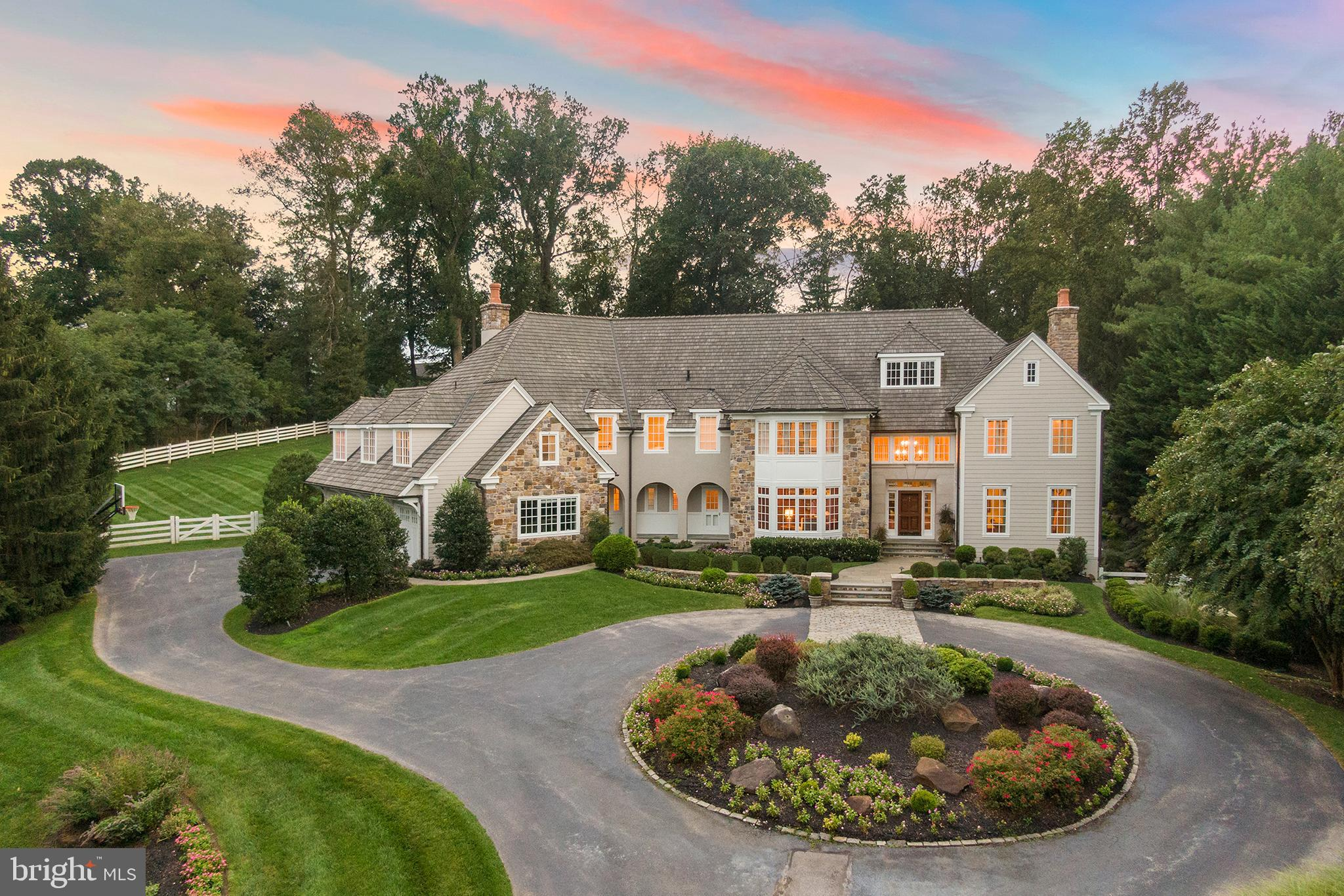 An idyllic Chester County setting is the backdrop for this fresh, highly styled 5 bedroom, 5.3 bath,turn-key estate home. Positioned on 2.3 professionally lit and landscaped acres with resort-quality amenities including terraces on all of the home's entertaining levels, a waterfall, koi pond and grotto, gorgeous swimming pool and spa, gas and wood-burning fire pits, and built-in grill, all ringed by mature evergreens for year-round enjoyment and privacy. A superior floor plan opens to a spacious volume reception Foyer with the straight-thru architecture leading to views of lawns and gardens. Designed for a seamless flow while entertaining, the Living and Dining rooms open to the entrance, striking just the right balance between formal and casual welcome. The home also offers an exceptional high-yield workspace with two beautifully outfitted home Offices. One provides direct access from the front turning circle creating that needed separation between work and family life. The Kitchen is as stunning as it is functional. Bright, well-planned connected! A suite of professional appliances, generous flat prep areas, and custom cabinetry form the perimeter around a large marble-topped seated center island. Steps away and warmed by western exposure through conservatory-sized windows, the Breakfast Room flows into the Great Room. One of the home's three fireplaces is highlighted by rich surround paneling with an over-look Loft adding height and dramatic appeal. Ascend a sweeping front staircase to a large Primary suite. A neutral color palette double exposure of eastern and western facing windows and a tray ceiling deliver a serene and relaxing experience.  A large spa bath and a truly spacious walk-in closet complete the primary suite. Four additional guest or family bedrooms complete this floor. The home's Lowest Level offers a full walk-out to the garden and terrace and is an exciting level of the house. The 2400 bottle temp-controlled Wine Cellar is detailed with hand-he
