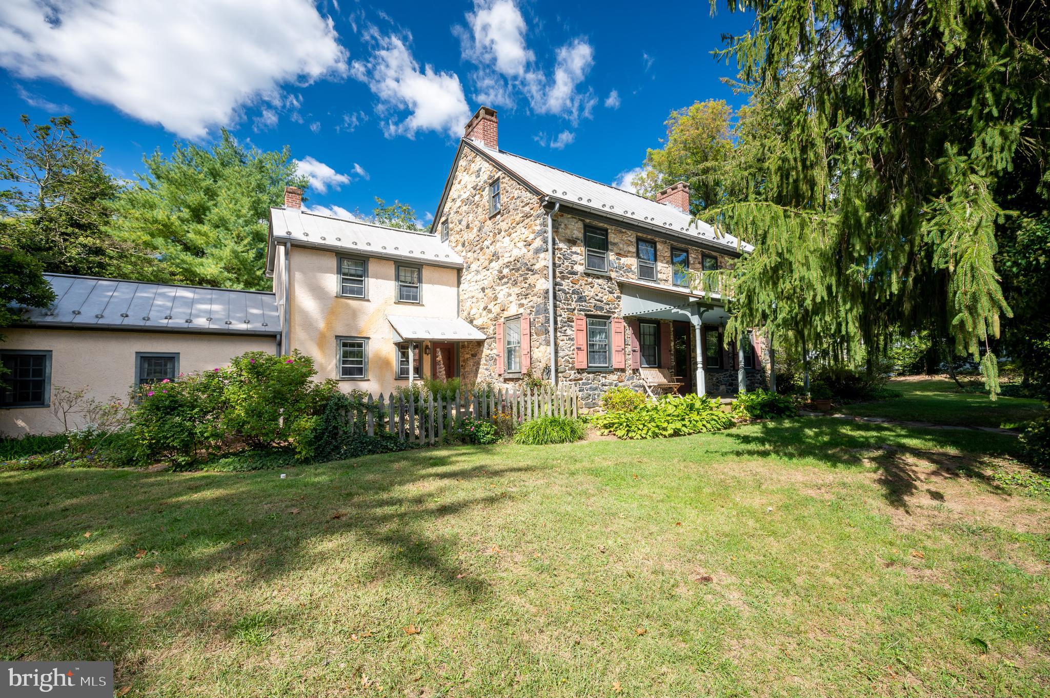 Rare opportunity to own a piece of history in the Red Clay Valley.  The original stone house was built in 1823 by the Montgomery on or near the site of a log cabin built by the Montgomery ancestors. In 1888 the home was purchased by the Mitchell family at a sheriff's sale. A two story addition was added shortly after along with Victorian features such as the front porch. Both the original house and the addition were stuccoed. The house stayed in the Mitchell family for over 100 years which it was purchased and restoration began. The current owners purchased the home in 1995 and over the course of 3 years finished the restoration process and added the wing to the home that includes the primary bathroom, laundry room, family room, kitchen, powder room, and office. A historical reproduction of an old barn was built as the garage. Native plants,   patio, and stone walls with stairway to back door were added to enhance the natural lay of the land. In 2001 an outbuilding in keeping with the architecture was built to house an Endless Pool. Inside the home you will find modern amenities like the nicely appointed kitchen with abundant cabinetry, stainless appliances and granite counters seamlessly blended with the original architectural features like the original cooking fireplace, stone entry step,  and 5 fireplaces. The original well has even been preserved under one of the additions as an architectural feature with access by a trap door covering the well protected by safety glass and lite from underneath. An updated primary suite is comprised of bedroom with fireplace, spacious dressing area with built-in cabinetry, smaller dressing area that leads to private bathroom and laundry room. A back staircase leads down to the breakfast room and kitchen. Main floor has a traditional feel with a front keeping room at the front door, den with corner fireplace, spacious front to back dining room, kitchen with breakfast room with wood stove, and family room with gas fireplace. While