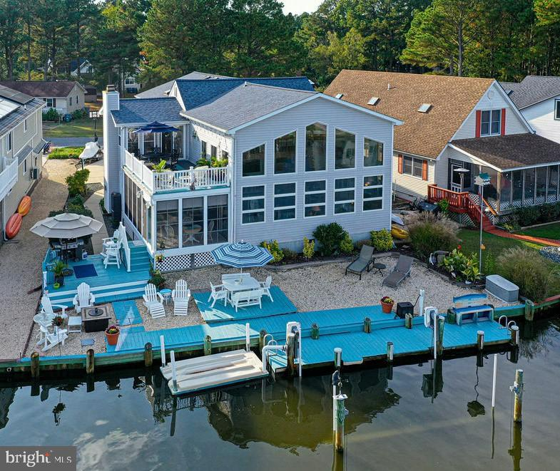 This awesome large beach house  has everything you need and want, is in a fantastic waterfront location right by open water, and has the best entertaining space for a large group!  Friends and family will gather in the kitchen /dining area which opens to the huge waterfront great room filled with windows.... OR gather on the 12x20 3 season sun room....OR gather on one of 2 sun decks.  Your boat is ready and waiting on the newer 8000 lb boatlift and your jet skis are parked on the floating jet ski dock.  You are less than one minute from the open waters of beautiful Manklin Creek and Isle of Wight Bay! The gorgeous oversized garage is super organized with lots of storage, a utility sink, shelving units & work area, and extra refrigerator.  For quiet time and privacy, this house boasts three dens/offices!  Owners will delight in the private stairway leading to the large primary suite with beautiful master bath and private office.  The other staircase leads to a loft overlooking the water, two more bedrooms, a full bathroom,  a den/office/fifth bedroom, and a pull down staircase leading to attic storage.  There is also one bedroom and full bathroom on the first floor, along with another den.  There are 3 zones for heating and cooling in this home! Recent updates include: new roof with architectural shingles in 2020; all new carpet 2021; insulated garage door 2021 controlled by your cell phone; hot water heater and washer/dryer recently new.  You have been dreaming of owning a beach home, and this home is your dream come true!